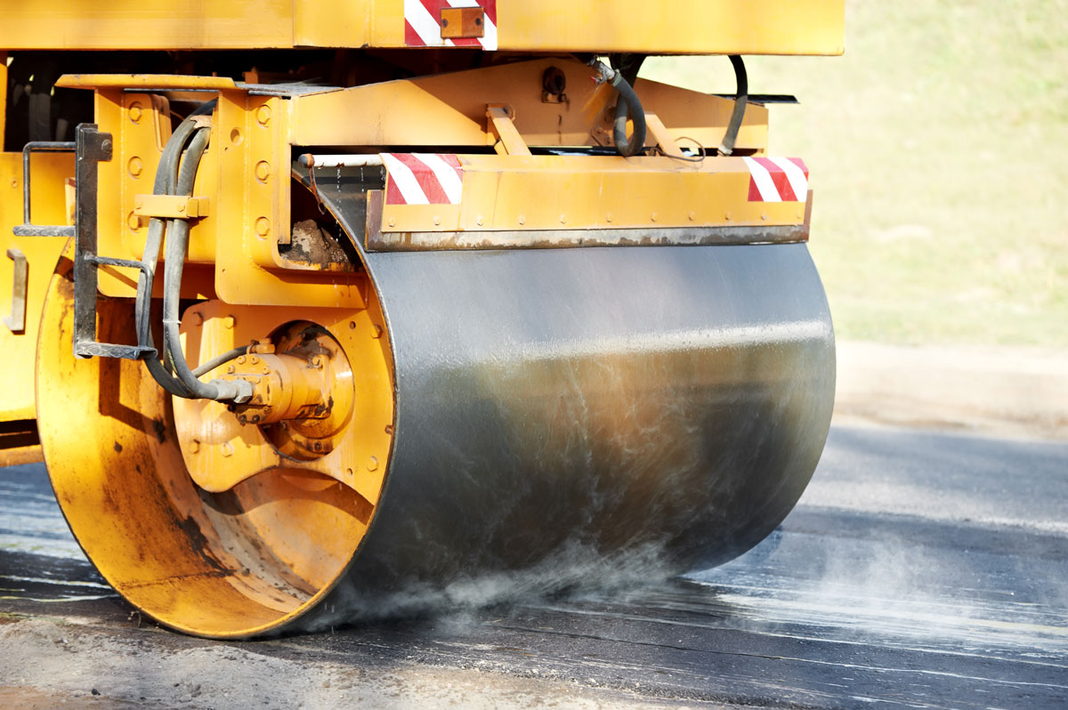 APS Chip Sealing and Paving asphalting a road with a roller